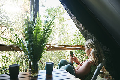 Buy stock photo Shot of a young woman using her cellphone while relaxing on a porch at a cabin