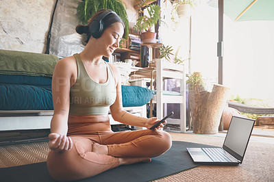 Buy stock photo Shot of a young woman using a cellphone and laptop while exercising at home