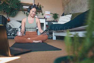 Buy stock photo Shot of a young woman wearing headphones and using a cellphone while exercising at home