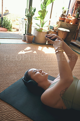 Buy stock photo Shot of a young woman wearing headphones and using a cellphone while lying on an exercise mat at home