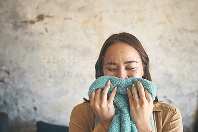 Buy stock photo Shot of a young woman smelling freshly washed laundry at home