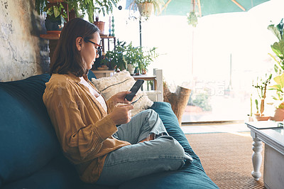 Buy stock photo Shot of a young woman using a smartphone and credit card on the sofa at home