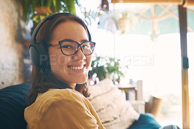 Buy stock photo Portrait of a young woman using headphones while relaxing on the sofa at home