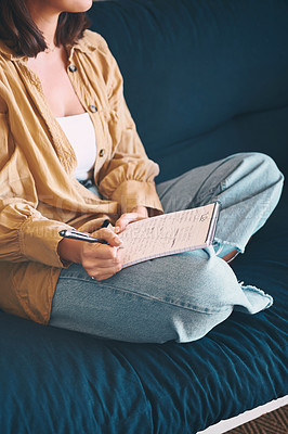 Buy stock photo Shot of an unrecognisable woman making notes while relaxing on the sofa at home