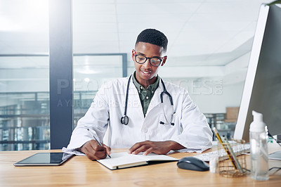 Buy stock photo Shot of a handsome young doctor sitting alone in his office at the clinic and writing in his notebook
