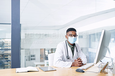 Buy stock photo Shot of a young doctor wearing a face mask and sitting at his desk in his office at the clinic