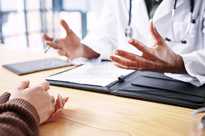 Buy stock photo Cropped shot of an unrecognizable doctor sitting with his patient and explaining her diagnosis during a consultation in the clinic