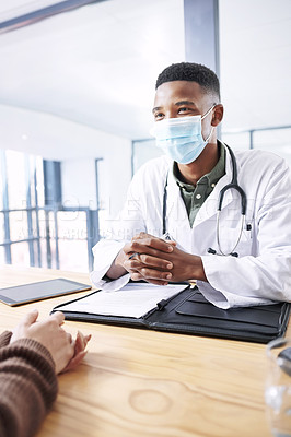 Buy stock photo Shot of a young doctor sitting with his patient and wearing his face mask during a consultation in the clinic