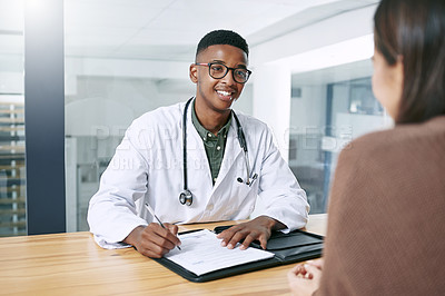 Buy stock photo Shot of a handsome young doctor sitting with his patient and writing a prescription during a consultation in the clinic