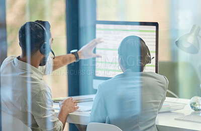 Buy stock photo Shot of two businesspeople discussing something on a desktop while working in a call center