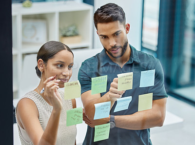 Buy stock photo Shot of two businesspeople brainstorming with sticky notes on a transparent wall