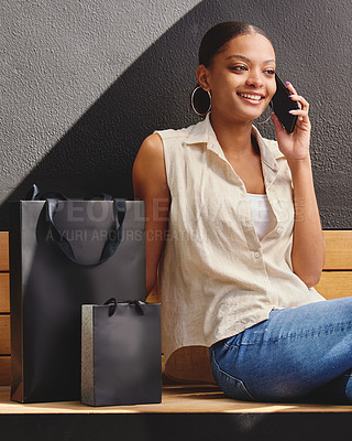 Buy stock photo Shot of a woman talking on her cellphone while sitting on a bench with shopping bags