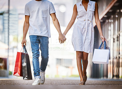 Buy stock photo Shot of a young couple walking hand in hand while holding shopping bags