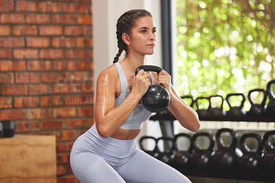 Buy stock photo Shot of a young attractive woman using a kettle bell in a  squatting position at the gym