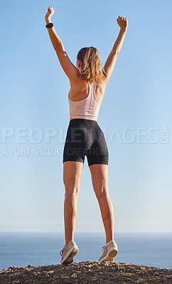 Buy stock photo Rearview shot of an unrecognizable and athletic young woman standing with her arms raised during her run in the mountains