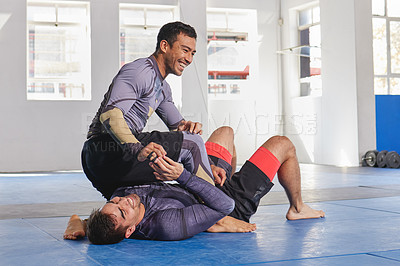 Buy stock photo Full length shot of a jiu jitsu sensei sparring with one of his students during a class
