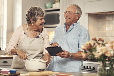 Buy stock photo Shot of a senior couple using a digital tablet while baking at home