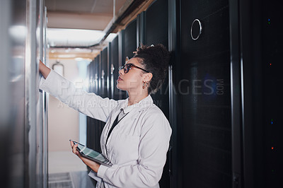 Buy stock photo Shot of a young woman using a digital tablet in a server room at work