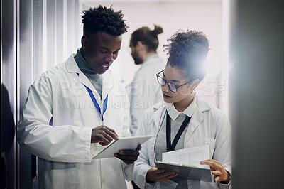 Buy stock photo Shot of two young workers using digital tablets in a server room at work