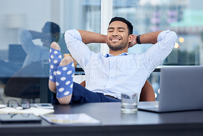 Buy stock photo Shot of a very satisfied businessman relaxing at his desk at work