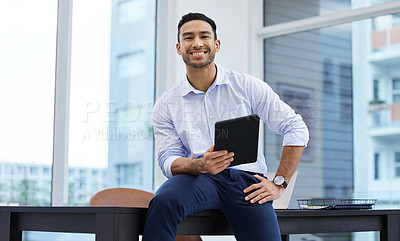 Buy stock photo Shot of a handsome young businessman sitting alone in his office and holding a digital tablet