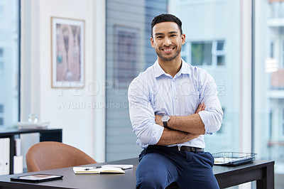 Buy stock photo Shot of a handsome young businessman sitting on his desk in the office with his arms folded