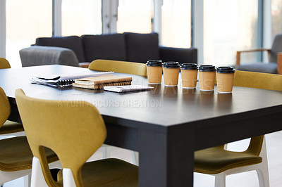 Buy stock photo Shot of coffee and paperwork on a desk in an empty office during the day