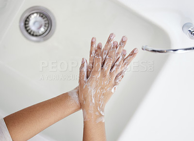 Buy stock photo Shot of an unrecognizable person washing their hands at home