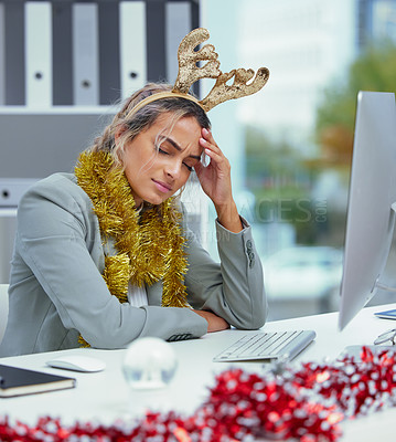 Buy stock photo Shot of a young woman suffering from an intense headache at her desk in the office
