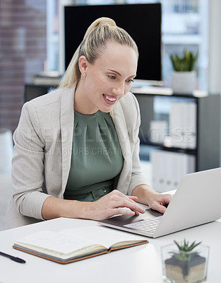 Buy stock photo Shot of a young businesswoman working at her desk using her laptop
