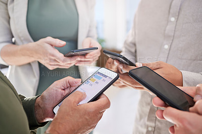 Buy stock photo Shot of a group of coworkers together using their smartphones