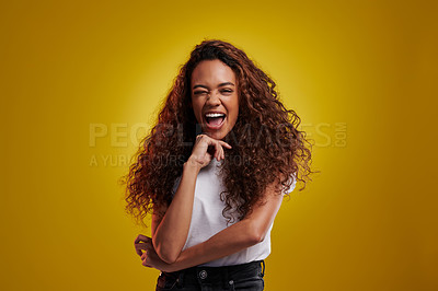 Buy stock photo Studio portrait of a young woman winking against a yellow background