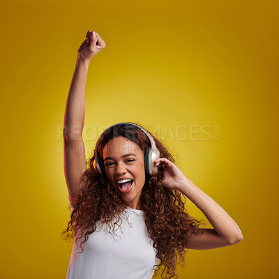 Buy stock photo Studio portrait of a young woman dancing while wearing headphones against a yellow background