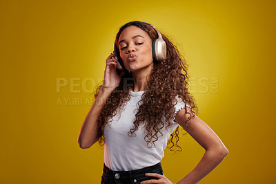Buy stock photo Studio shot of a young woman wearing headphones against a yellow background