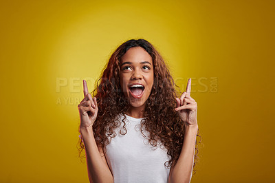 Buy stock photo Studio shot of a young woman pointing against a yellow background