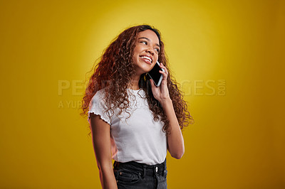 Buy stock photo Studio shot of a young woman talking on a cellphone against a yellow background