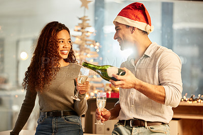 Buy stock photo Shot of two young businesspeople celebrating Christmas at work