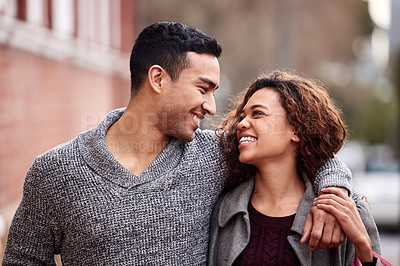 Buy stock photo Cropped shot of an affectionate young couple enjoying a day in the city