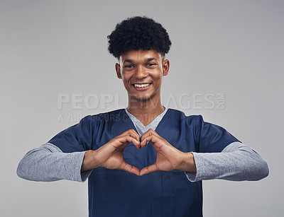 Buy stock photo Shot of a male nurse forming a heart shape with his hands while standing against a grey background