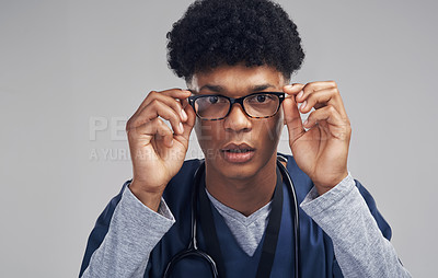 Buy stock photo Shot of a male nurse wearing glasses while standing against a grey background