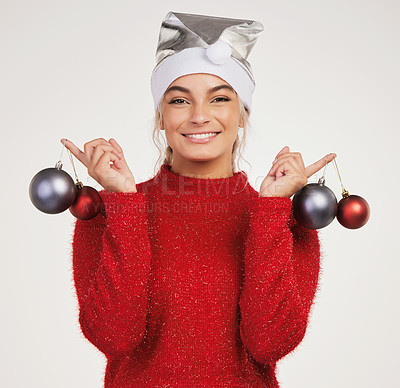 Buy stock photo Studio shot of a young woman holding Christmas decor against a grey background