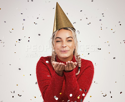 Buy stock photo Studio shot of a young woman wearing a party hat and blowing confetti against a grey background