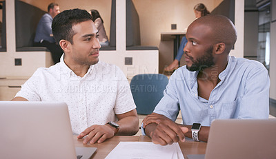 Buy stock photo Shot of two young businessmen sitting together in the office and having a discussion while using laptops