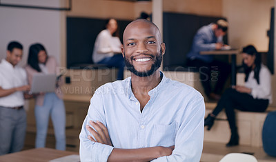 Buy stock photo Shot of a handsome young businessman standing in the office with his arms folded