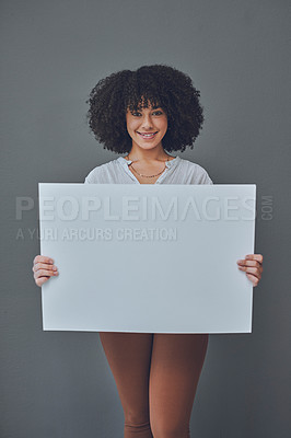 Buy stock photo Studio portrait of a young woman holding a blank poster against a grey background