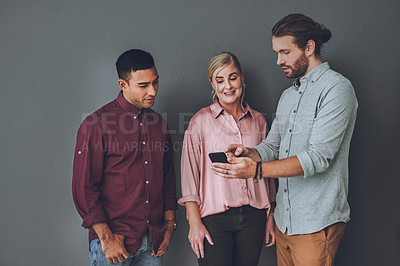 Buy stock photo Studio shot of a group of people looking at something on a cellphone against a grey background