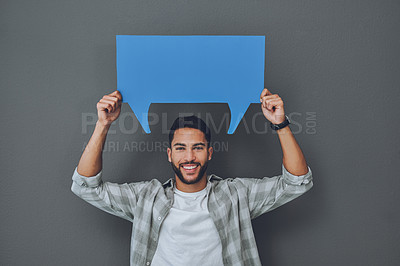 Buy stock photo Studio portrait of a young man holding a blue speech bubble against a grey background