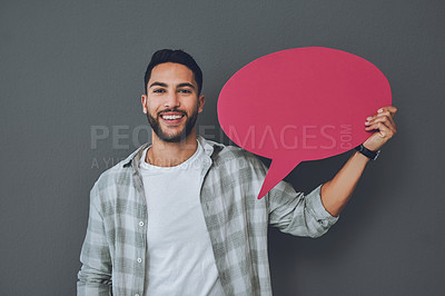 Buy stock photo Studio portrait of a young man holding a pink speech bubble against a grey background