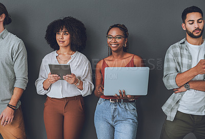 Buy stock photo Studio portrait of a young woman using a laptop while standing alongside other people against a grey background