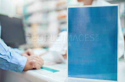 Buy stock photo Closeup shot of a sign on the counter of a chemist while an unrecognizable pharmacist and customer talk in the background